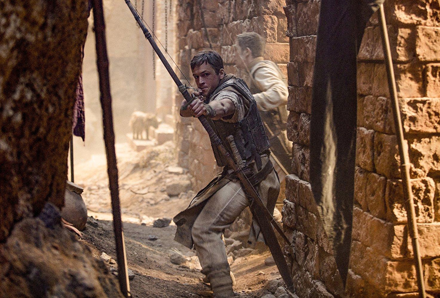 Taron Edgerton con l'arco in mano in una scena da Robin Hood: L'origine della leggenda